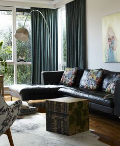 Leather sofa, florals, and deep curtains.