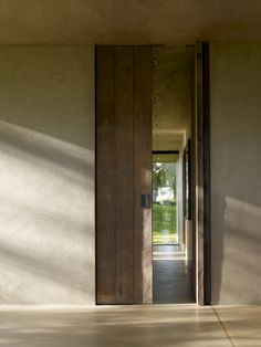(San Joaquin Valley Residence) A rustic vocabulary was developed in response to the agricultural vernacular, resulting in a neutral palette of cement plaster, reclaimed wood posts and planks, steel, board formed concrete, and water elements.