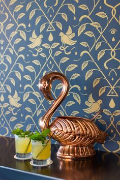 Navy wallpaper with a gold bird and leaf pattern, behind a copper flamingo punch bowl