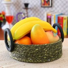 "Fruit Basket: A round basket with round lift handles. Made in Sabai Grass and bamboo. Ideal fruit basket for your dining table.  Sabai grass products are made primarily in the Mayurbhanj area of West Bengal and the Northern parts of Odisha. This grass is then fashioned into mats, bags, table accessories, floor coverings and furniture. 8.6"" x 5.3"""