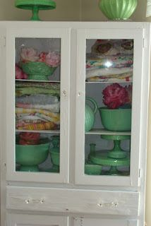 Folded vintage tablecloths, aprons, and serving dishes displayed in an old white cabinet.