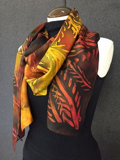 """This striking scarfmeasures 14"""" x 72"""" and is sure to turn heads. Adorned with beautiful tones of black, red, orange, brown and yellow, showcasing a fern pattern throughout. 100% Luxurious silk, design"""