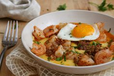 Grits: 4 cups water salt 1 cup yellow grits (not instant) 1 cup (4 ounces) grated sharp white cheddar 1 tablespoon unsalted butter 1 jalapeño, seeded, diced ¼ cup heavy cream or milk freshly ground pepper  Shrimp: 8 ounces andouille sausage 3 garlic cloves, minced 1 pound shrimp, peeled and deveined ¼ cup beer ¼ cup low-sodium chicken broth 1 tablespoon butter 4 large eggs salt 1 tablespoon chopped fresh tarragon