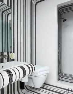 A guest bath is sheathed in Bisazza tile; the sink is by Kohler, and the shower and sink fittings are by Waterworks.