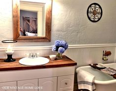 love the white vanity with the butcher block countertop w/ matching frame on mirror!