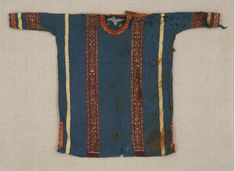 This tunic is 76.7 cm long and 112.3 cm wide. It is made of plain woven linen, with wool tapestry woven inserts and appliqué. It was thought to have been made between the 7th and 9th centuries. The tunic is currently in the Textile Museum of Canada.