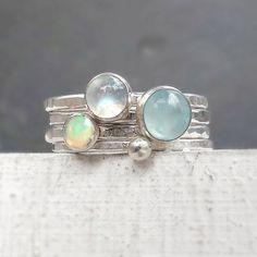 Vurige opaal, regenboog Maansteen en pastel blauwe Aquamarijn maken een prachtige verklaring wanneer gecombineerd in deze reeks van stapelbare ringen. Pastelkleuren die opvallen! Voltooiing van de reeks van vier ringen is een band van de spacer instellen met een heldere fijn zilver. De ring-bands zijn gemaakt van gerecycled zilver en gegeven een geciseleerde textuur met gepolijste afwerking.  DETAILS: -6mm Aquamarijn cabochon op een ~ 2mm gehamerd sterling band; -5mm regenboog Maansteen…