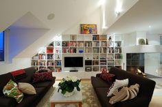 Platsbygda bokhyllor i en vindsvåning kan utformas efter dina behov och önskemål. Att fylla en hel vägg med böckerkan blisom en målning eller ett konstverk. I det här fallet har hyllan fler funktioner. Förutom böcker fylls den med skulpturer, förvaring, prydnadsföremål och tv:n förstås.