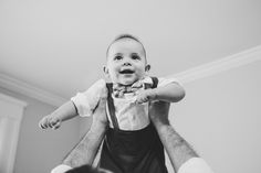 A photojournalistic portrait of a baby boy being lifted in the air during an in home lifestyle family photo session in Boston, Massachusetts - Gina Brocker Photography