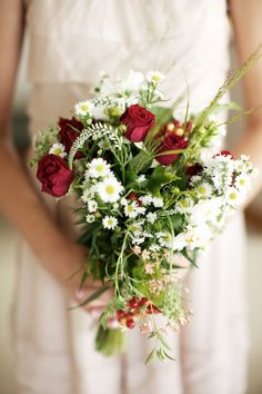 This bouquet is like a little bit of spring mixed with winter! The red roses and greenery bring the holiday colors and the filler flowers (lysimachia, chamomile and Queen Anne's Lace) add a touch of spring season!