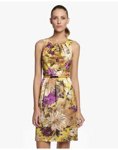 Vestido corto, sin mangas y escote redondo. Con estampado floral, detalle de pliegues en el pecho y la falda y cinturón a tono.
