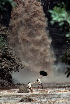 Steve McCurry: Two men try to cross a monsoon swollen river after the bridge was swept away in Goa India. For months there is no rain, and then there is too much. Half the world's people survive at the whim of the monsoon. Goa India, India Trip, Steve Mccurry Photos, Steve Mccurry Portraits, World Press Photo, Foto Art, We Are The World, Ansel Adams, Incredible India