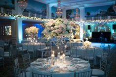 A magical wintery reception with white flowers, twinkle lights and blue uplighting. Image by Eli Turner.