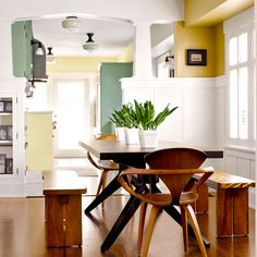 Columned half-walls with an arched beam overhead set off the dining room while allowing air and light to flow.   Kitchen ceiling fixtures: @schoolhouseelec