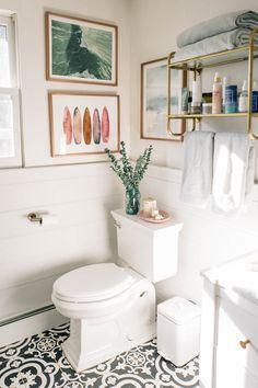 costal calm bathroom design // stencil tile floor // white vanity // gold brass shelves
