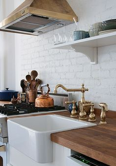 Farm style kitchen with butchers basin, brass cooker hood, brass victorian styled taps and mixer. Rustic wall painted white - all makes for a very keen kitchen