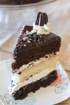 Layers of chocolate and vanilla cake are filled with vanilla frosting, crushed Oreos, and topped with a chocolate ganache.