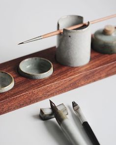 Part of a ceramic and mahogany watercolour palette set. The ceramic pieces are thrown with a clay body rich in iron and have an assortment of crackle glazes applied. Brush holders, miniature inkwells and water-pots are set into the hollows in the wood. Below this sits an ink dip pen, thrown off the hump and laying on an extruded rest, both are glazed in a similar fashion with layered white and green. All the pieces are reduction fired to near cone nine, around one-thousand two-hundred and…