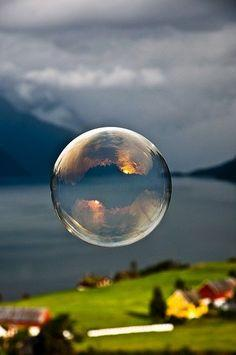 mountain sunset in the bubble :)   Morning light reflected in a soap bubble over the fjord by Odin Hole Standal