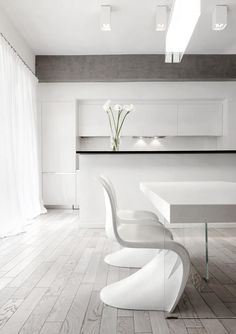 Clean white kitchen with dining table with cool lucite legs