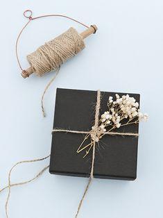 Envoltorio de papel negro, cordón de rafia natural y flores
