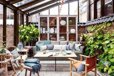 Porche acristalado con sofá, butacas de madera, banqueta, manta y armario vitrina_377400