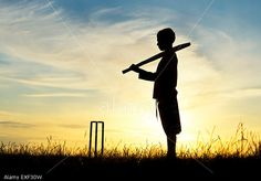 Silhouette of a young boy playing cricket in long grass at sunset. UK. (Stock Photo) © Tim Gainey / Alamy http://www.alamy.com https://www.alamy.com/stock-photo-silhouette-of-young-boy-playing-cricket-against-a-sunset-background-85154185.html