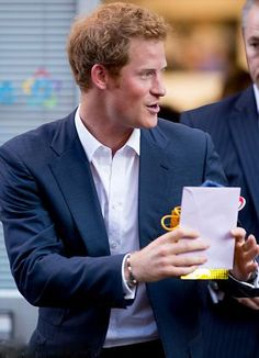 Presents for a prince...Prince Harry holds the gift and accompanying card. Speaking at the opening of the charity photo show he also admitting to having a lovely cuddle with the tiny baby boy who will one day probably be king.