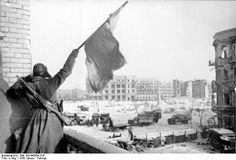 Russian soldier waving a red flag at a building off the central square in Stalingrad, Russia, Jan-Feb 1943