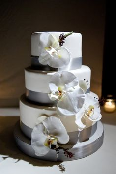 beautiful winter wedding cake with silver ribbon and white orchids