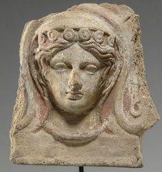 Etruscan terracotta antefix, 4th century B.C. Molded in the form of a facing veiled female head, perhaps a maenad, her hair center parted, wearing a diadem ornamented with disks, and a thick necklace, originally framed by a shell-shaped fan with palmettes in relief, a tendril preserved to the right, the remains of pigment throughout, including white for the face, pink for the lips, black for the eyes and red for the hair, 18.4 cm high. Private collection