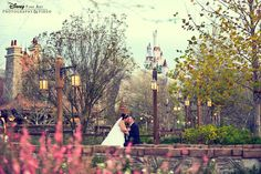 Bride and groom in New Fantasyland at Magic Kingdom Park - with Beast's Castle in the distance