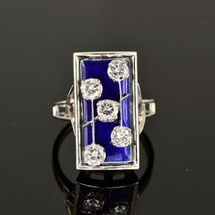 An unique late Art Deco ring made by CUSI, an Italian jewelry maker in Milan since 1886.  Geometric diamond and blue enamel ring accented with dramatic lines and colour contrast.  Five bright old transitional brilliant cut diamonds (approx. 1.26 ctw) float on a rectangular panel of royal blue enamel.  The open pierced shanks are rendered in 18 Kt white gold, tested, and marked with designer hallmarks.  $3,585.66.