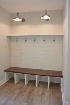 Beautifully illuminated mudroom. Complete with bench, storage and hooks for coats and purses. The shiplap adds a great contrast against the plain walls.