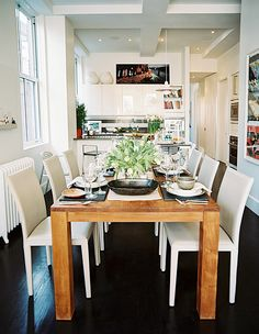 Modern Dining Room Photo - A wooden table and white chairs in a dining space open to a white kitchen