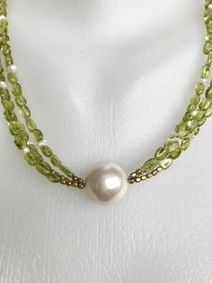 Beautiful multi strand necklace, 12mm big round Shell Pearl centre piece, necklace decorated with 5x2mm peridot beads, tiny brass beads, 2x1mm rice pearls, gold filled seed beads with lobster clasp, 20 inches in length and weighs 40 grams. Ready to ship. Thank you for looking. This order