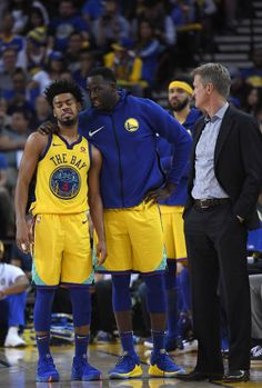 Quinn Cook Draymond Green and head coach Steve Kerr of the Golden State Warriors stand and talk during a break in the action of an NBA basketball...