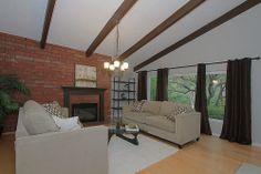 Brown beam ceilings, brick wall with brown mantle fireplace.  Walls are Benjamin Moore Revere Pewter.  WilburHomeStaging.com