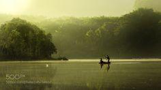 2 fisherman on small boat in warm morning lake by NuttKomolvanich