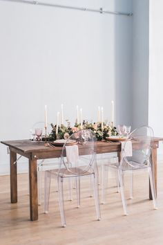 Neutral tone centerpiece for a long harvest table and tapered or candlestick candles. Accented with ghost chairs. Modern and Rustic wedding ideas