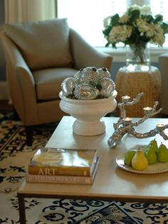 Gather similar items together for maximum impact. In this living room, a bowl of silver acorns, platter of fruit and a vase full of flowers create a pleasing flow of accessories. Design by Linda Woodrum.