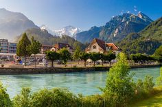 Train station and Aare river in Interlaken, important tourist center in Bernese Highlands, Switzerland. The Jungfrau is visible in background - Buy this stock photo and explore similar images at Adobe Stock Bali, Santa Monica, Bungalow, Mountains, Nature, Travel, Europe, Law School, Covered Front Porches