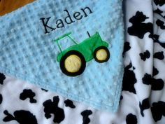 Personalized Baby Blanket- baby blue and cow print   baby boy tractor- 30x35 baby stroller blanket  I have fell in love with this!! Colors of his room, cow spots and tractor and his name-- oh my so so so cute!
