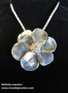Sterling Silver and 14kt yellow gold flower pendant. Each petal is a fingerprint of a grandchild.  McNulty Jewelers design
