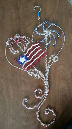 Wire wrapped beaded sun catcher with fireworks and flag.