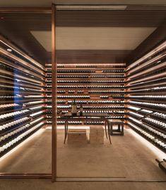 Nesta casa em São Paulo, assinada pelo Studio MK27 e Lair Reis, a adega tem prateleiras levemente inclinadas e iluminação que destaca as garrafas de vinho.
