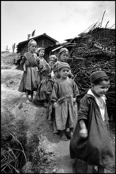 by Philip Jones Griffiths  - ALGERIA. 1962. Children in a regroupment camp in the Kabylie region. The French troops occupied the high ground under the fluttering Tri-color flag Magnum Photos Photographer Portfolio