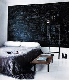 An entire wall painted in chalkboard paint in the bedroom of German fashion designer Hanne Graumannr