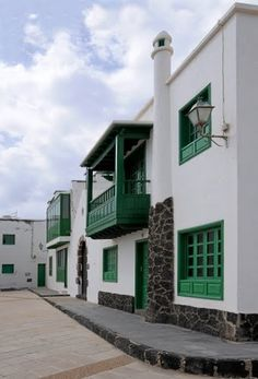 Spain - Lanzarote - Caleta de Famara / Houses at the harbour harbour --- classic green doors, balconies & windows, chimneys as well as volcanic stone at the foundation & used decoratively Travel Around The World, Around The Worlds, Southern Europe, Canary Islands, Travel Goals, Mansions, Green Doors, Architecture, House Styles