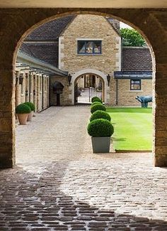 Tipping House Estate has an archway that divides the main estate from the cobbled stable courtyard. The present from the past.... The stables are older at Tippermere, and there's a fountain in the centre of the yard, but the archway is something like this.  Stone stable and courtyard